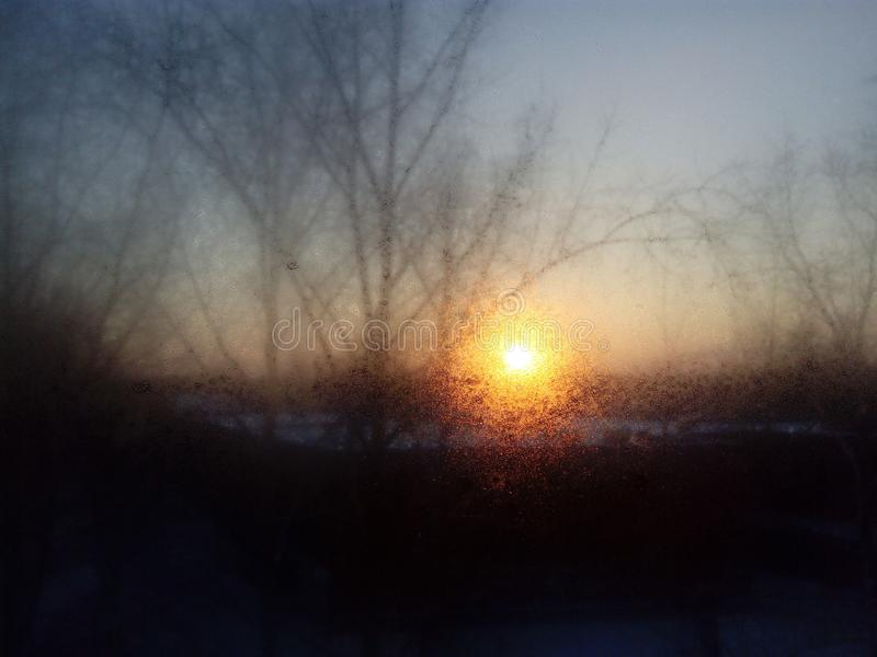 Vroege ijzige de lenteochtend door het mistige ijzige venster stock fotografie