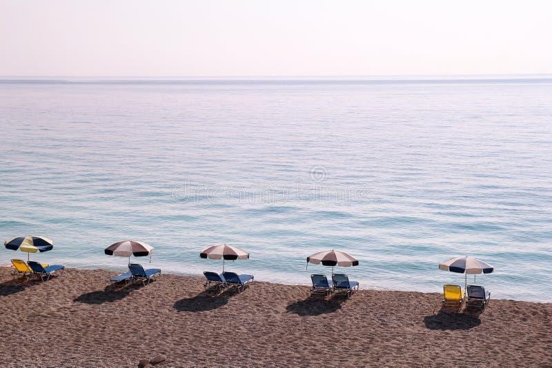 Vroege ochtend op zandig strand zonder mensen met lege chaise zitkamers, zonbedden, sunshades, de parasol van de de zomerparaplu, stock foto's