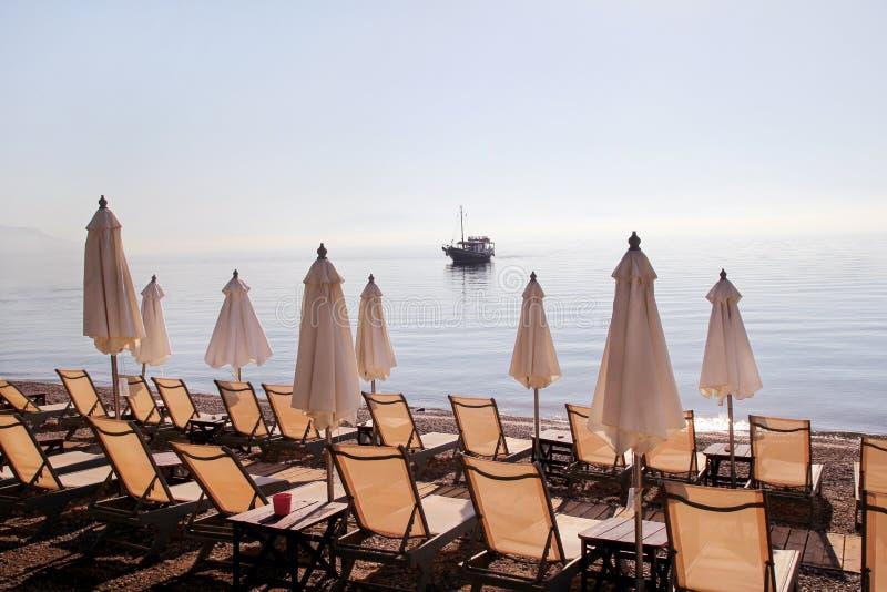 Vroege ochtend op zandig strand zonder mensen met lege chaise zitkamers, zonbedden, sunshades, de parasol van de de zomerparaplu, royalty-vrije stock foto's