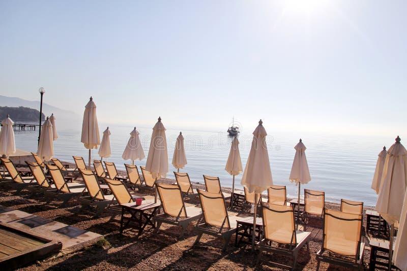 Vroege ochtend op zandig strand zonder mensen met lege chaise zitkamers, zonbedden, sunshades, de parasol van de de zomerparaplu, stock afbeeldingen