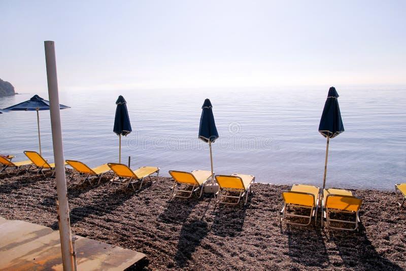 Vroege ochtend op zandig strand zonder mensen met lege chaise zitkamers, zonbedden, sunshades, de parasol van de de zomerparaplu, royalty-vrije stock fotografie