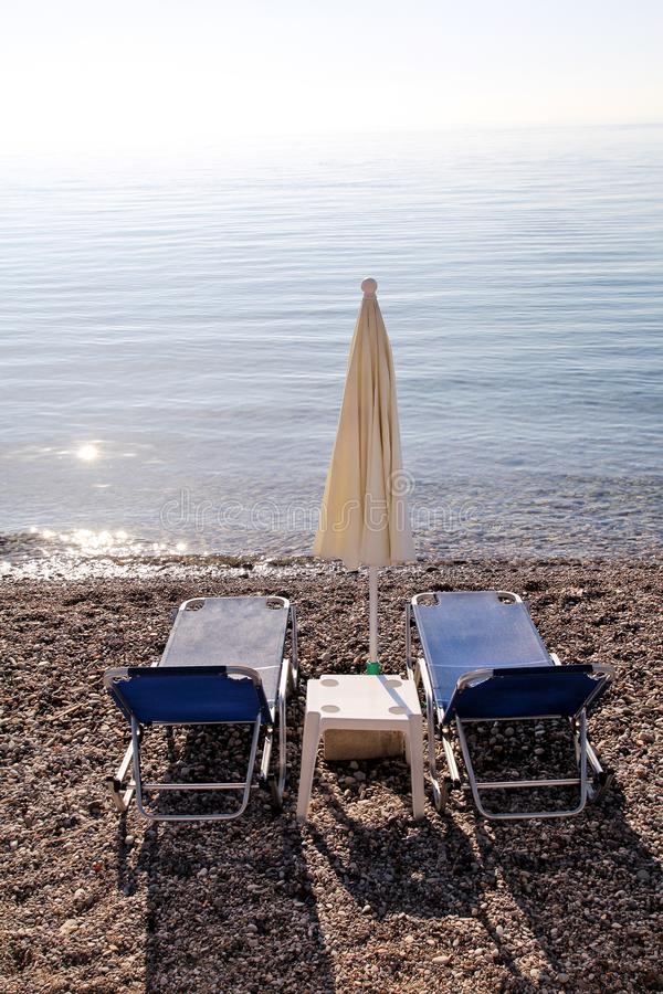 Vroege ochtend op zandig strand zonder mensen met lege chaise zitkamers, zonbedden, sunshades, de parasol van de de zomerparaplu, royalty-vrije stock afbeelding