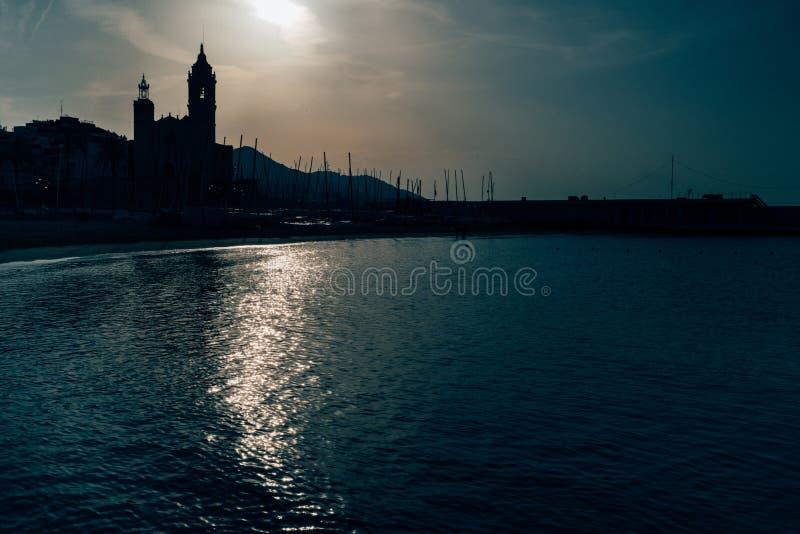 Vroege ochtendmening van de kust in Sitges-stad dichtbij Barcelona in Catalonië, Spanje met Parroquia DE Sant Bartomeu i Santa Te stock foto