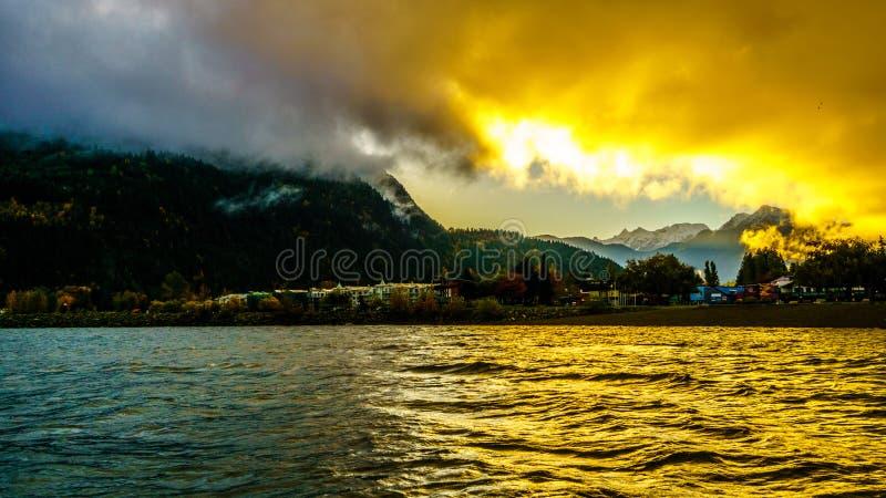 Vroege Ochtendzonsopgang en Donkere Wolken over de stad van Harrison Hot Springs royalty-vrije stock afbeelding