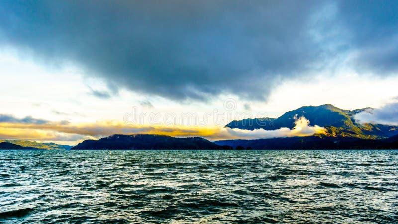 Vroege Ochtendzonsopgang en Donkere Wolken over Harrison Lake stock foto's