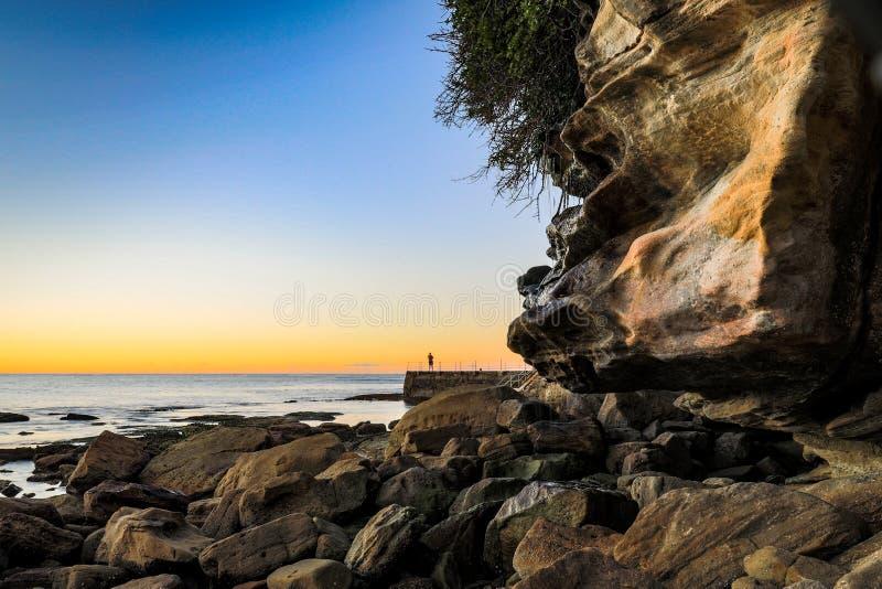 Vroege ochtendzwemmer bij oceaanbaden tegen blauwe hemel en rotsachtige kustlijn royalty-vrije stock foto's