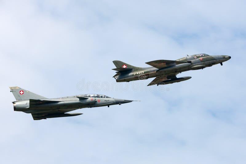 Vroegere Swiss Air-Luchtspiegeling III vechtersvliegtuigen j-2012 van Krachtdassault hb-RDF die in vorming met een Venter Hunter  stock afbeeldingen