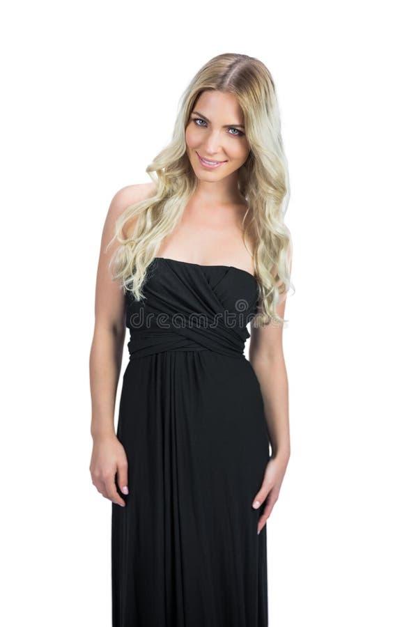 Vrolijk aantrekkelijk blonde met het zwarte cocktailkleding stellen royalty-vrije stock foto