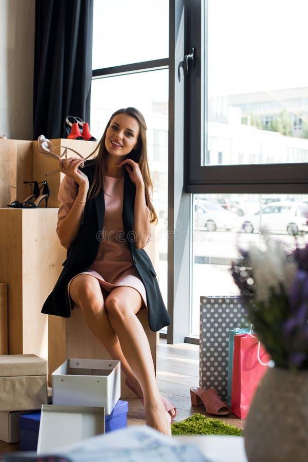 vrolijk aantrekkelijk meisje die modieuze hoog gehielde schoen houden en bij camera glimlachen stock fotografie