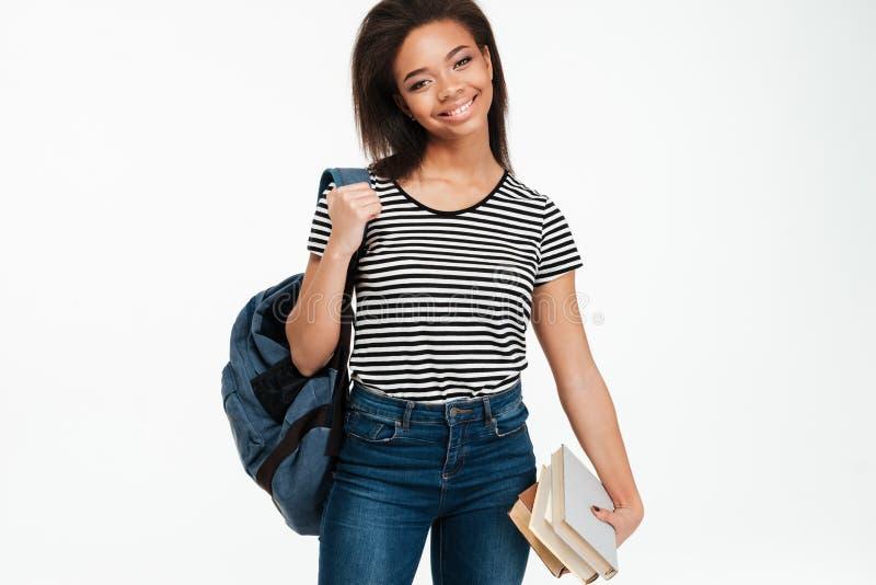 Vrolijk Afrikaans studentenmeisje die rugzak dragen en boeken houden stock foto