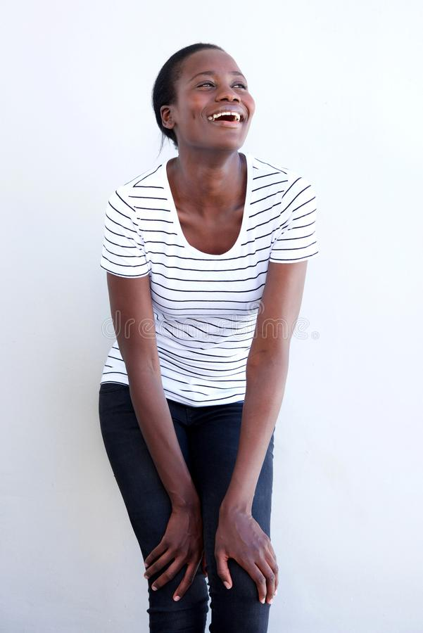 Vrolijk Afrikaans wijfje die tegen witte achtergrond lachen royalty-vrije stock fotografie