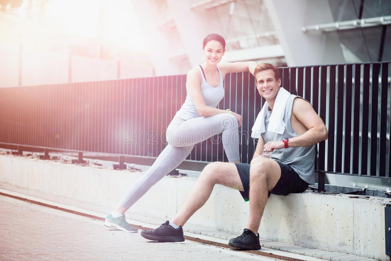Vrolijk atletisch paar die samen na training rusten stock foto