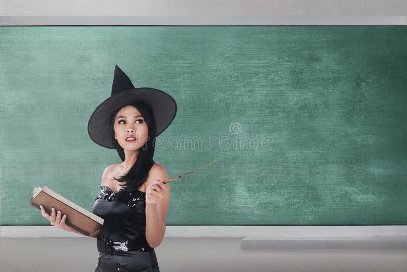 Vrolijk Aziatisch de holdingsboek en toverstokje van de tovenaarsvrouw stock fotografie