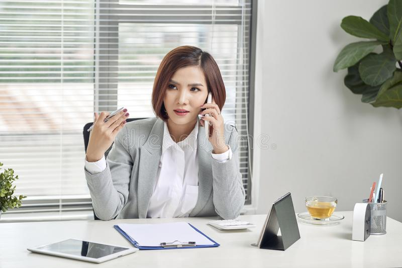 Vrolijk Aziatisch wijfje die op mobiele telefoon spreken terwijl het zitten op bureau met laptop Bedrijfsvrouw in toevallig maken royalty-vrije stock foto's