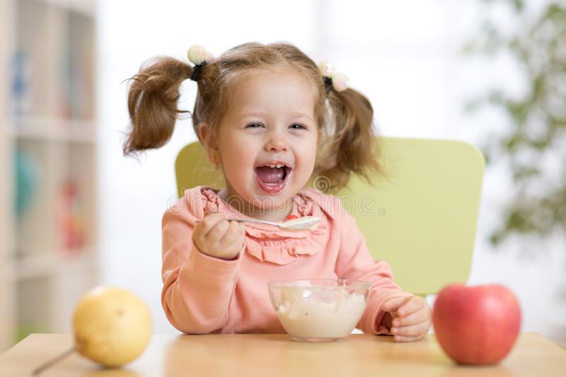 Vrolijk babykind die voedsel zelf met een lepel eten stock afbeelding