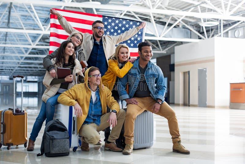 Vrolijk bedrijf van vrienden die zich met banner bij de luchthaven bevinden royalty-vrije stock afbeeldingen