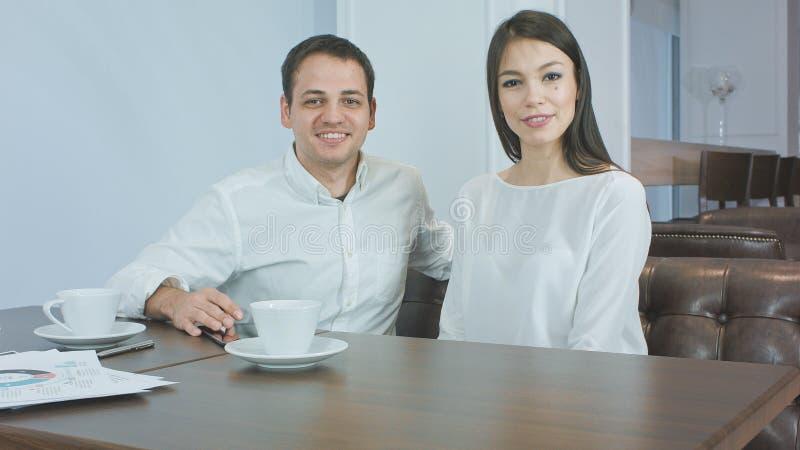 Vrolijk bedrijfspaar die aan de camerazitting spreken in een koffie royalty-vrije stock afbeeldingen