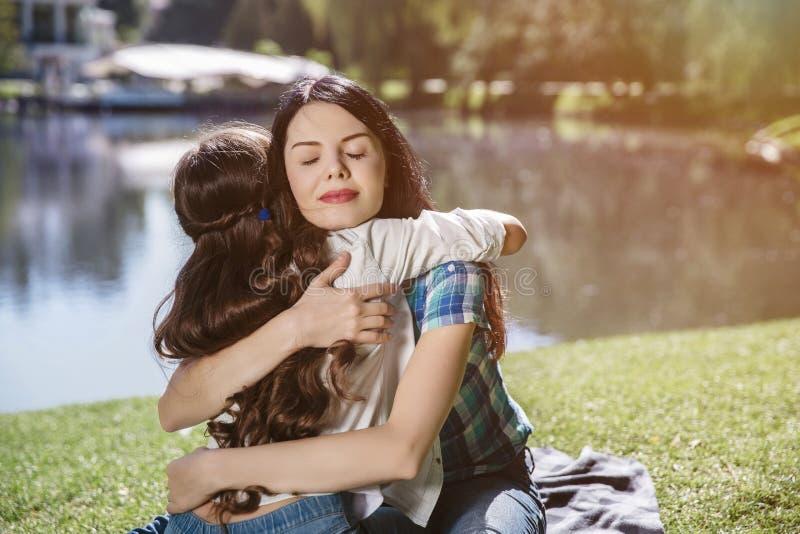Vrolijk beeld die van moeder en dochter elkaar omhelzen De vrouw houdt ogen gesloten Zij is zeer gelukkig Zij zijn stock afbeelding