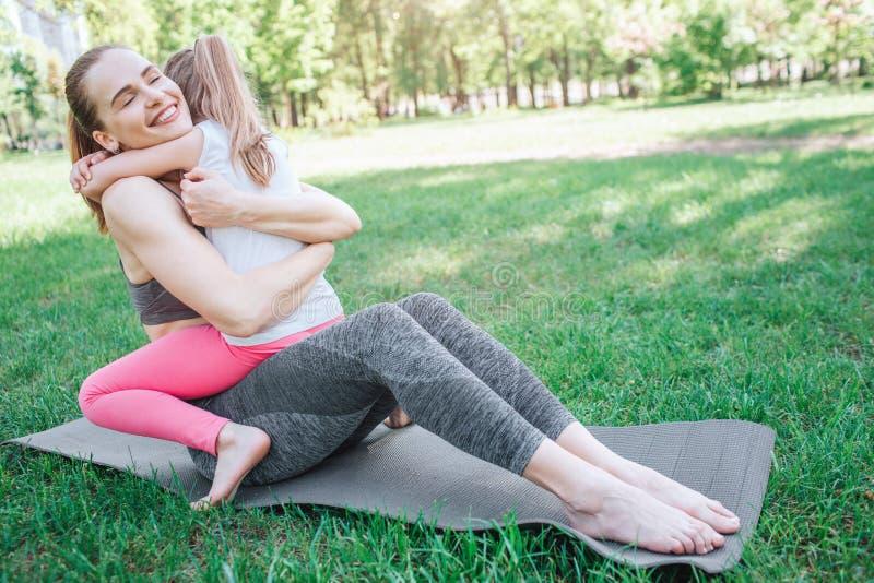 Vrolijk beeld van Volwassen vrouw die haar jong geitje koesteren De vrouw zit op carimate terwijl het kleine meisje op haar mamma stock fotografie