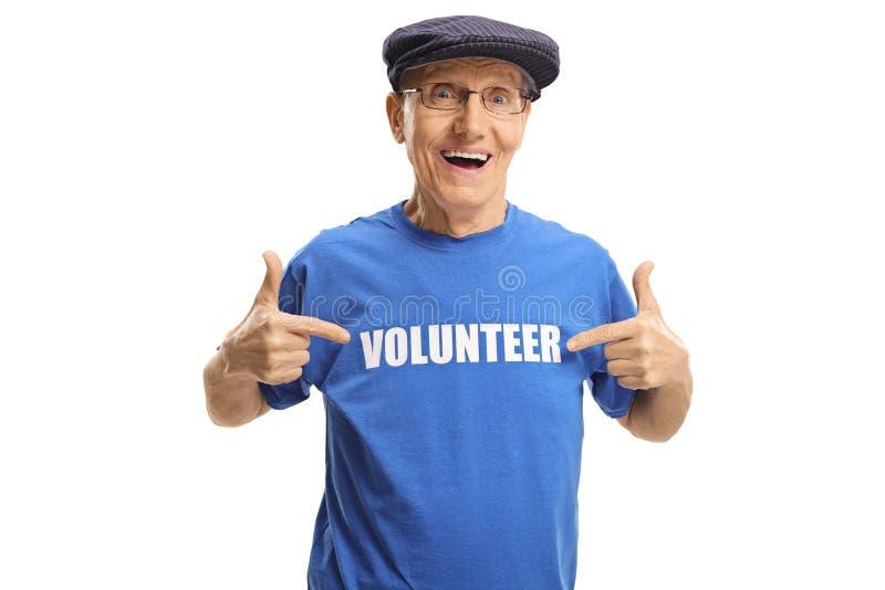 Vrolijk bejaarde dat een vrijwilligers ondertekende t-shirt draagt en op het richt royalty-vrije stock afbeeldingen