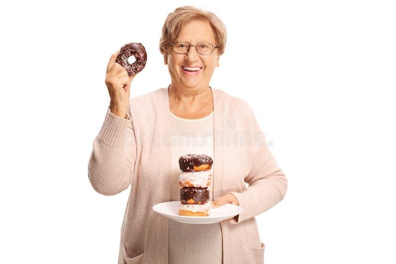 Vrolijk bejaarde die een plaat van doughnuts in één hand en één doughnut in de andere hand houden royalty-vrije stock afbeeldingen