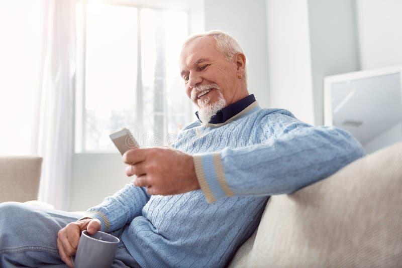 Vrolijk bejaarde die terwijl het drinken van koffie texting stock foto