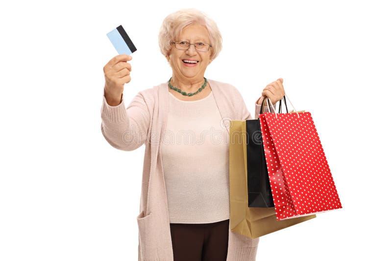 Vrolijk bejaarde met een creditcard en het winkelen zakken royalty-vrije stock foto