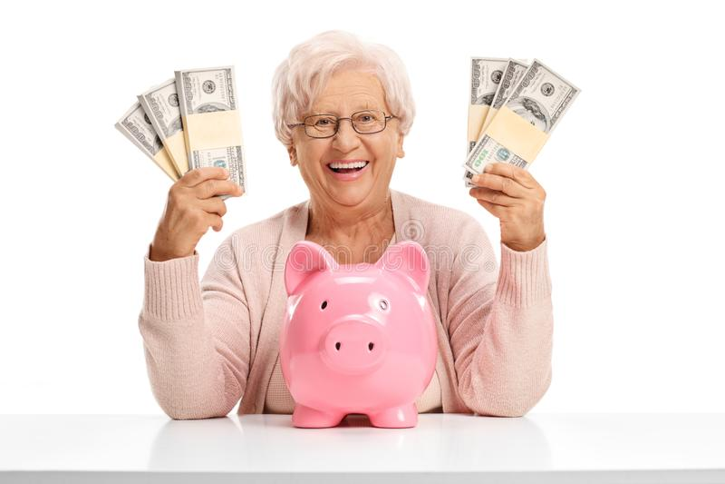 Vrolijk bejaarde met een piggybank en geldbundels royalty-vrije stock afbeelding