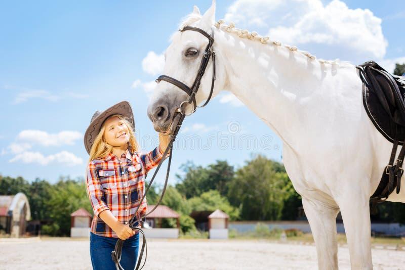 Vrolijk blonde-haired die meisjesgevoel door schoonheid van paard wordt geamuseerd stock foto's