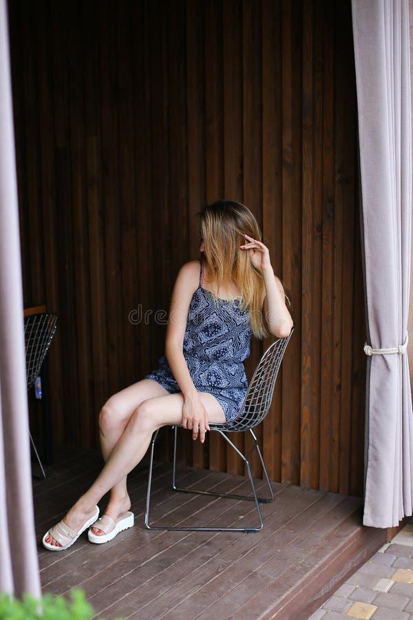 Vrolijk blondemeisje die dichtbij restaurant lopen en camera bekijken stock foto