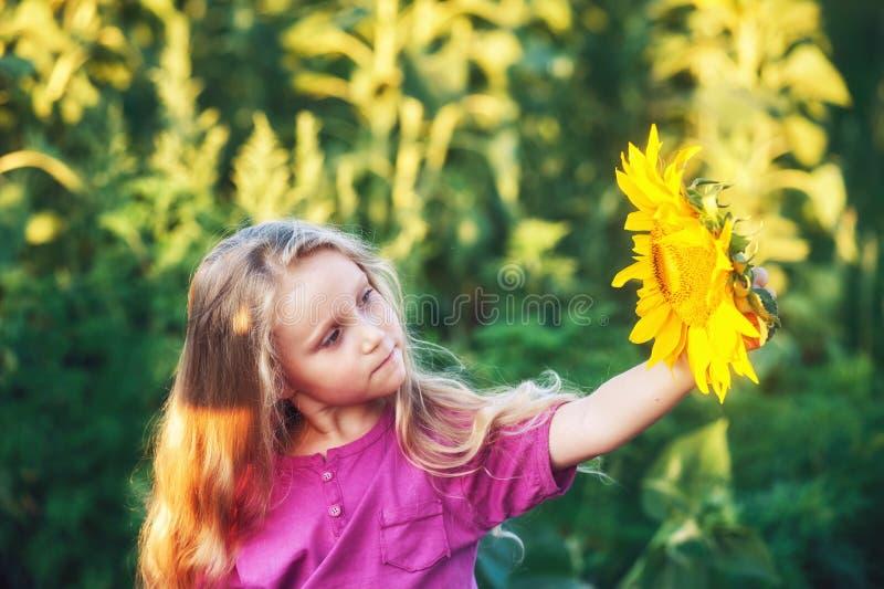 Vrolijk blondemeisje die een zonnebloembloem in haar handen houden stock afbeeldingen