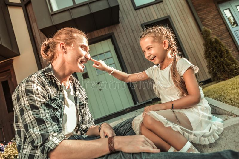 Vrolijk blondemeisje die grote verhoudingen met haar vader hebben royalty-vrije stock foto