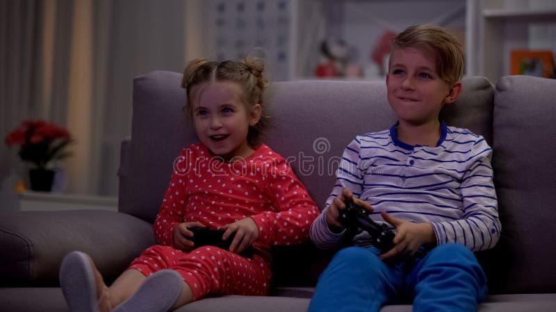 Vrolijk broer en zuster het spelen videospelletje die console gebruiken bij nacht, vrije tijd stock afbeeldingen