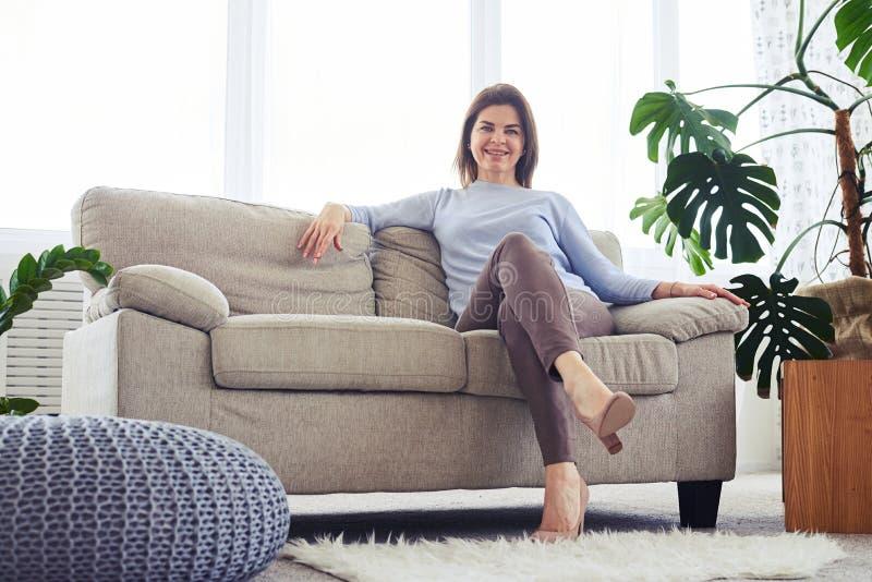Vrolijk brunette die rust op bank in heldere woonkamer hebben stock foto