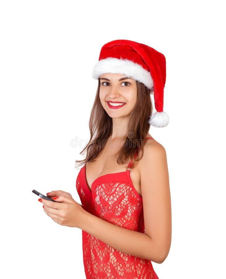 Vrolijk charmant jong meisje in Kerstmishoed die celtelefoon met behulp van emotionele vrouw in de rode die hoed van de Kerstman  royalty-vrije stock afbeeldingen