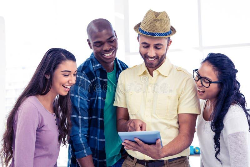Vrolijk creatief team die tabletpc met behulp van royalty-vrije stock afbeeldingen
