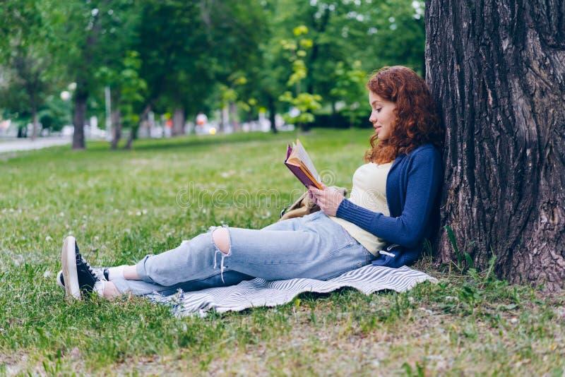 Vrolijk de lezingsboek van het roodharigemeisje in openlucht in park het glimlachen het ontspannen op gras stock foto's
