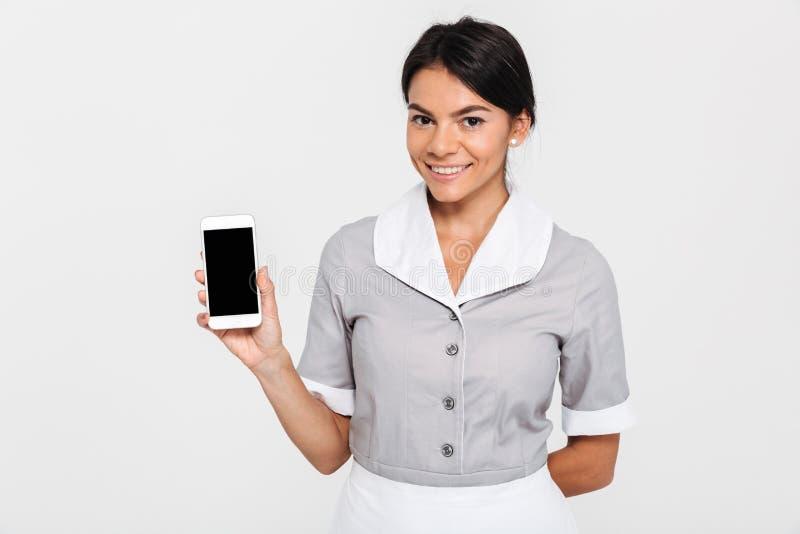 Vrolijk donkerbruin meisje in grijze eenvormige tonende lege mobiele scre royalty-vrije stock afbeelding