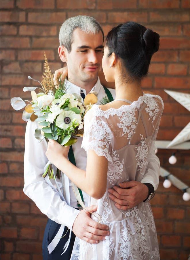 Vrolijk echtpaar die dichtbij de bakstenen muur dansen stock fotografie