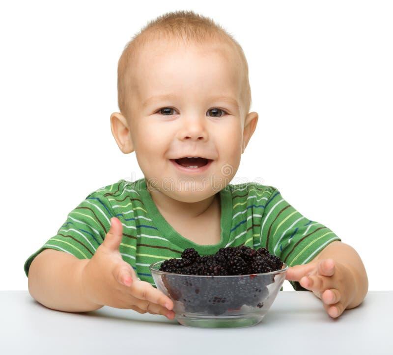 Vrolijk eet weinig jongen braambes royalty-vrije stock afbeeldingen
