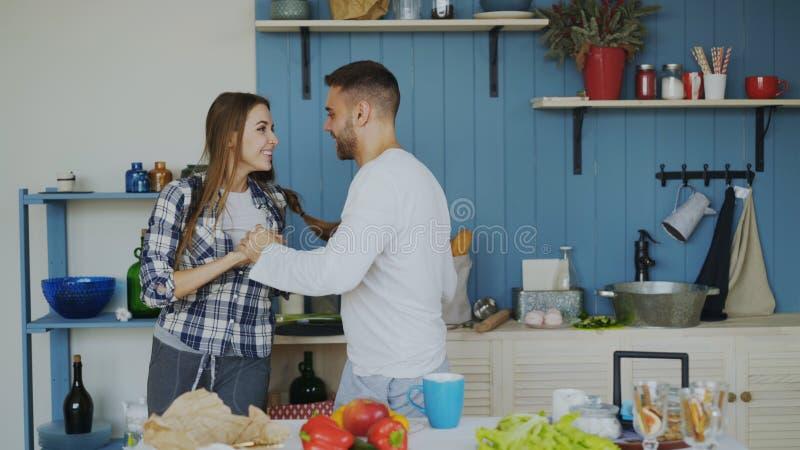 Vrolijk en aantrekkelijk jong paar die in liefde samen Latijnse dans in de keuken thuis op vakantie dansen stock afbeeldingen