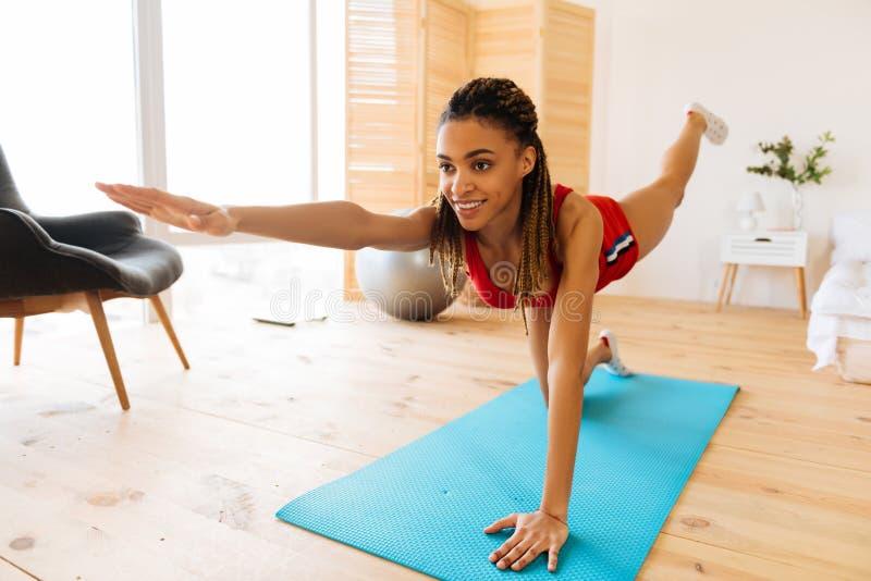 Vrolijk en geactiveerd vrouwengevoel terwijl thuis het doen van yoga royalty-vrije stock fotografie