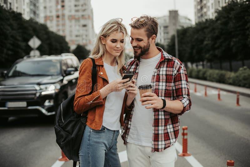 Vrolijk geinteresseerd jong paar die zich op straat bevinden stock foto