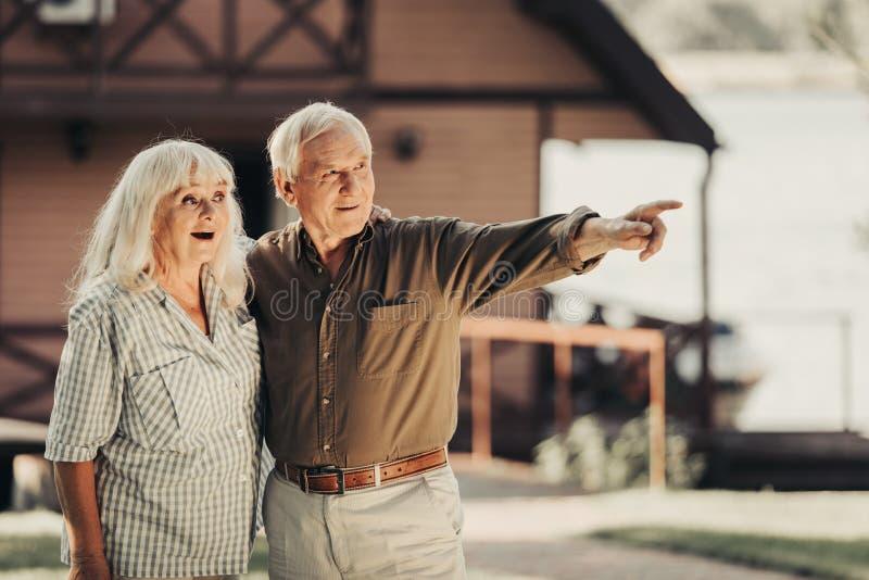 Vrolijk geinteresseerd oud paar die grote verbazing tonen stock afbeeldingen