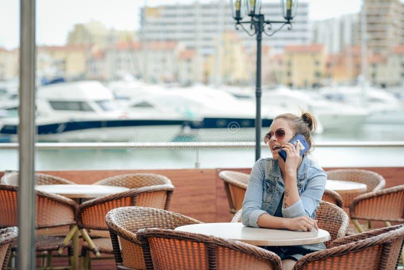 Vrolijk gelukkig glimlachend mooi wijfje die gebruikend smartphone in restaurant op de achtergrond van de luxejachthaven spreken  stock fotografie
