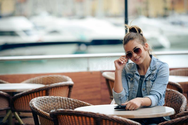 Vrolijk gelukkig glimlachend mooi wijfje in restaurant op de achtergrond van de luxejachthaven stock afbeeldingen