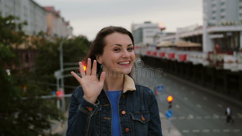 Vrolijk, gelukkig, het glimlachen meisje de status op de brug, verzendt kussen, heeft pret, bekijkt de camera 4K royalty-vrije stock foto's