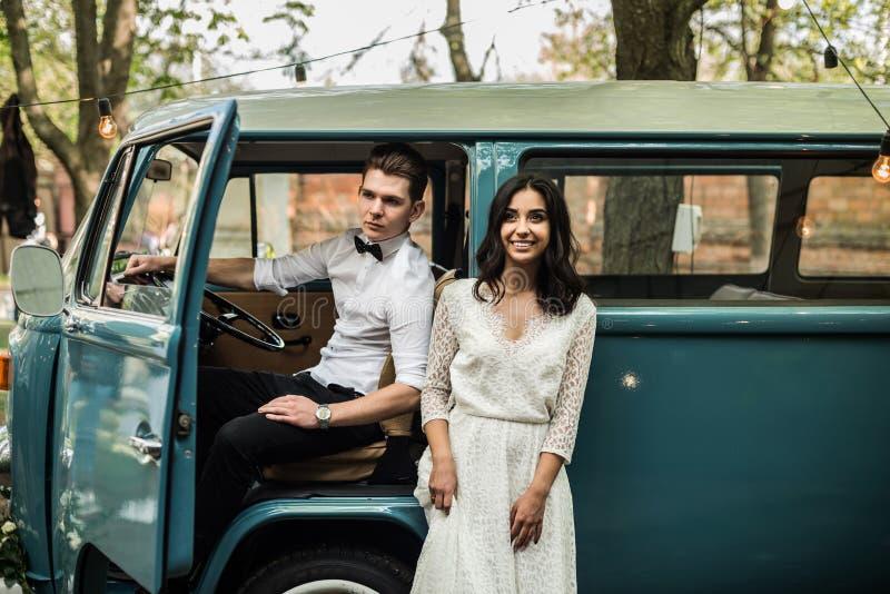 Vrolijk gelukkig jong paar dichtbij retro minivan Close-up stock foto