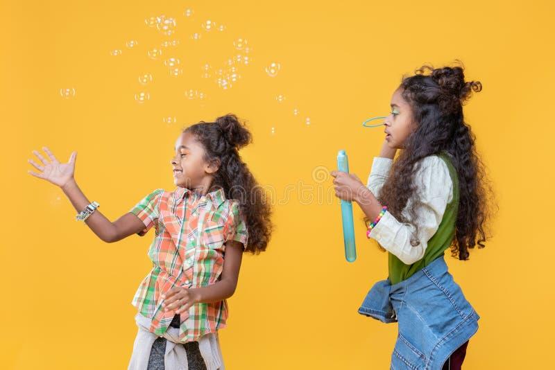 Vrolijk gelukkig meisje die de zeepbels vangen royalty-vrije stock afbeelding