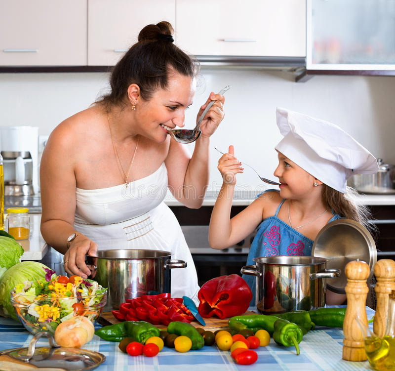 Vrolijk gelukkig meisje die moeder helpen aan kok royalty-vrije stock foto's